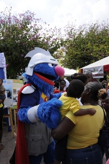 Super Grover shows a child some love.