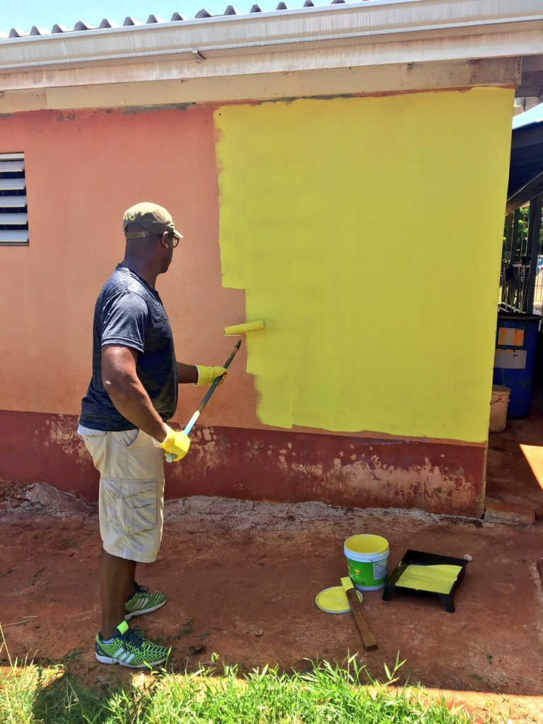 Marlon Hill painting a wall