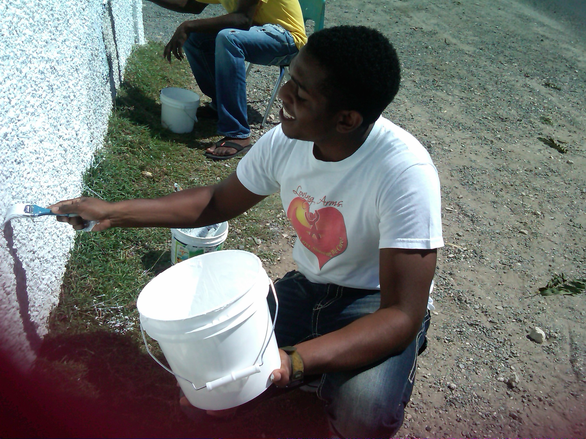 Loving Arms Youth Club members painting at Newlands Basic School.